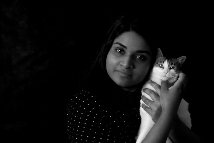 Portrait of woman holding cat against black background