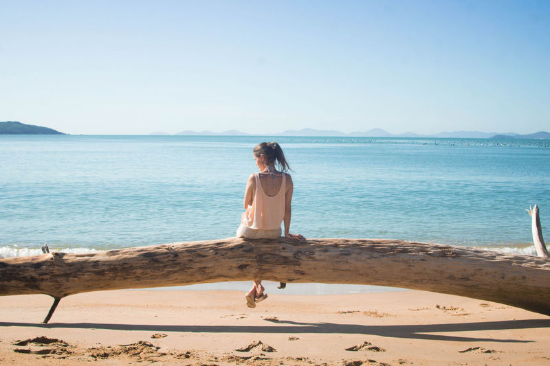 Rear View Of Woman Sitting On Fallen Tree At Beach Against Clear Sky