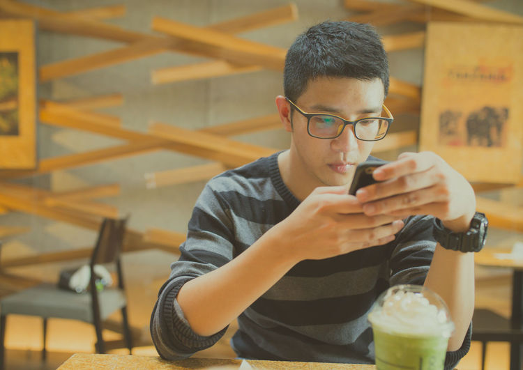 Man using mobile phone while sitting in cafe