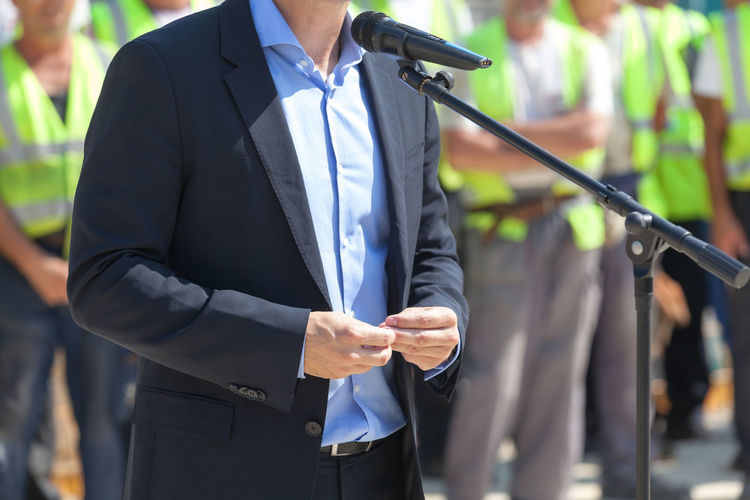 Midsection Of Man Giving Speech While Workers Standing In Background