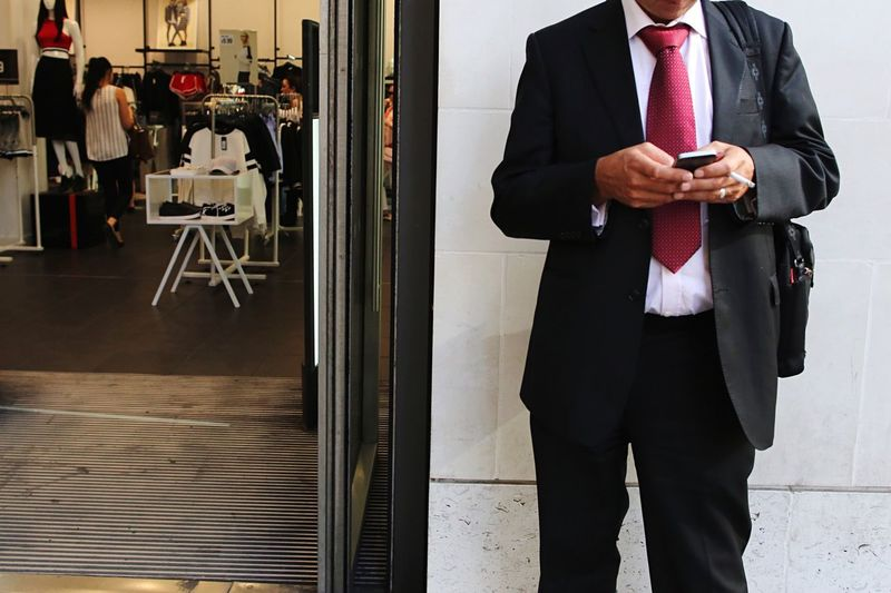 A businessman on the phone in city of London, UK Office Worker Suit Smoking Smoke Cigarette  Phone City Of London Bussinesswoman One Person Standing Men Midsection Front View Indoors  Suit Business Real People Clothing Business Person Wireless Technology Holding Well-dressed Adult Formalwear Businessman Males  Office Menswear