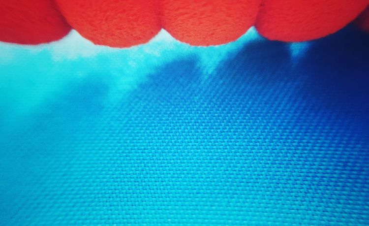 Abstract of an orange pencil foam grip against blue fabric background. Abstract Abstract Photography Backgrounds Background Bright Blue Orange