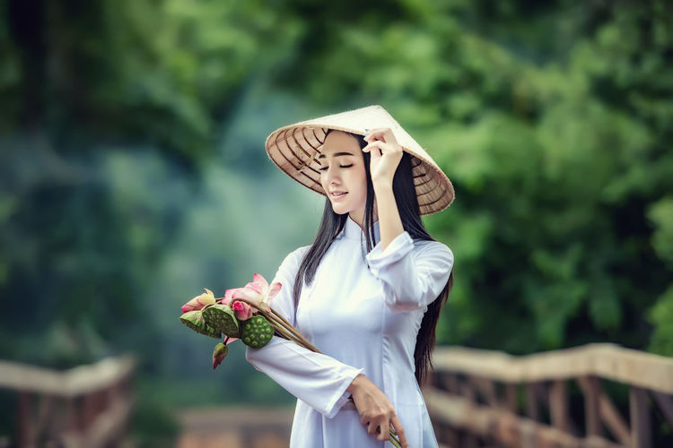 Woman wearing conical hat while holding flowers and pods against trees