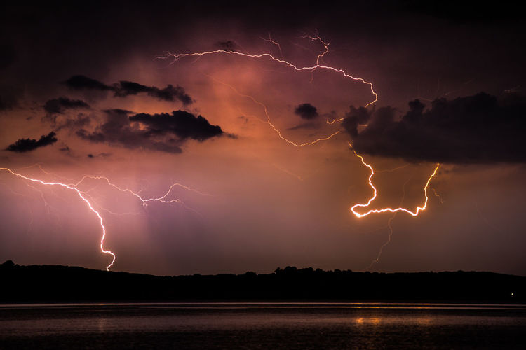 Lightning over calm lake at night