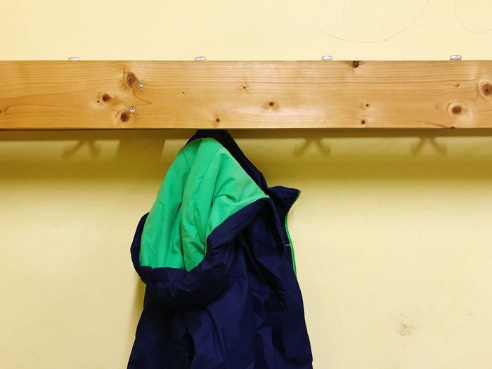 Close Up Of Clothes Hanging On Coathanger Against Wall