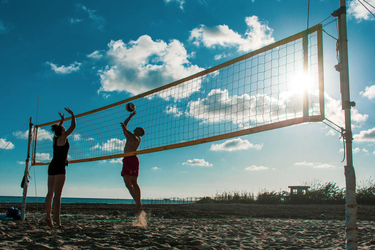Man and woman playing volleyball against cloudy sky during sunny day