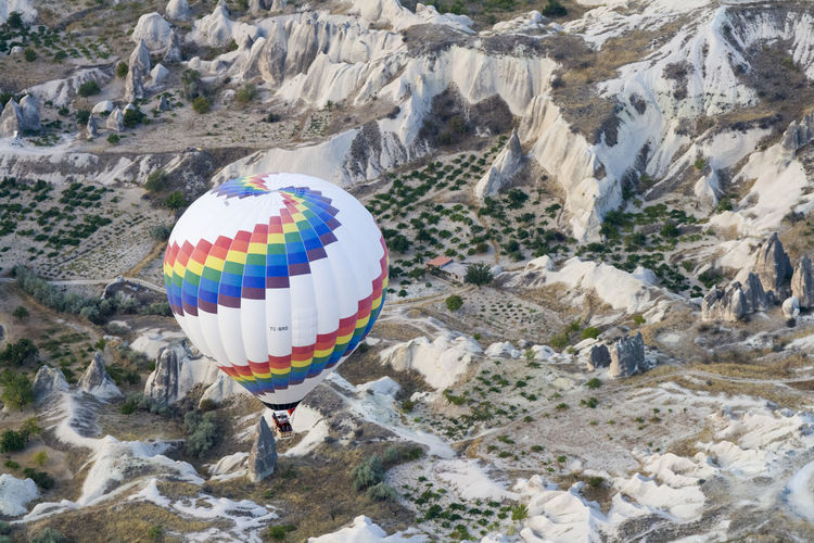 High angle view of hot air balloon over rock formations at cappadocia