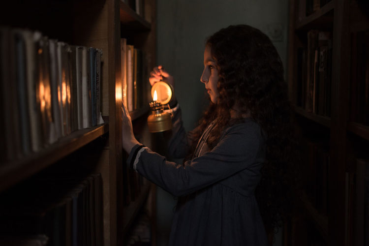 Side view of woman looking at illuminated lamp