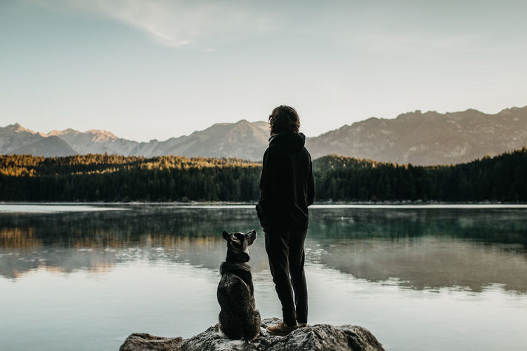 Girl and dog are standing on a rock in front of lake Eibsee Bayern Germany Bayern Germany Eibsee Silhouette Standing Beauty In Nature Dog Girl Guy Husky Lake One Animal One Person Pet Owner Rear View Rock - Object Scenics - Nature Women A New Beginning