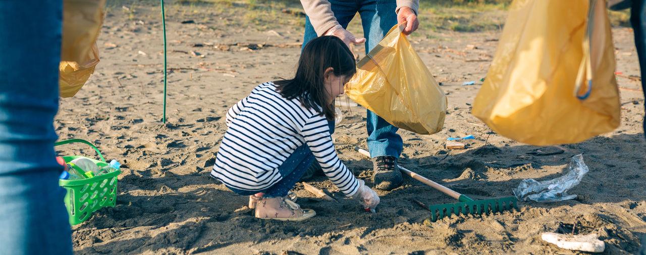 Girl picking up garbage at beach