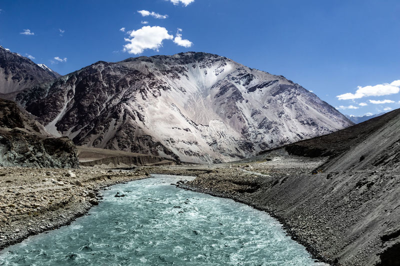 River flowing by mountain against sky