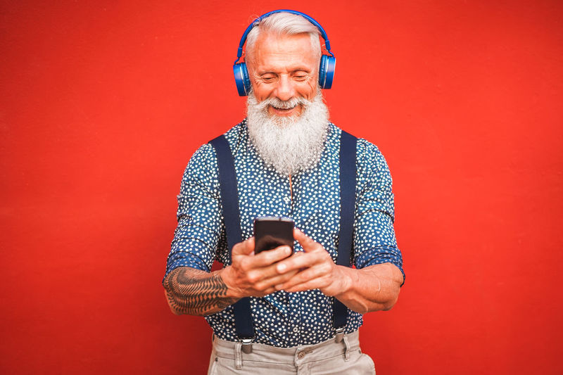 App Background Beard Bearded Cell Cellphone Color Communication Cool Day Device Elderly Fashion Fun Grey Happy Headphones Hipster Holiday Influencer Isolated Lifestyle Listening Male Man Mature Media Model Modern Moment Music Mustache Network Older  Pensioner person Phone Playlist Red Senior Smartphone Social Summer Tattoo Tech Technology Texting Trend Trends Trendy