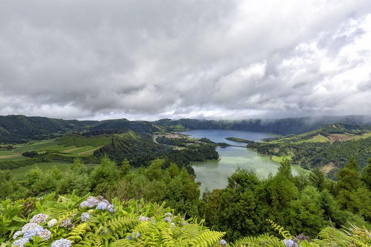 Vibrant view of the village of Sete Cidades in Sao Miguel on the Azores. Sao Miguel Azores Açores Sete Cidades Hike Trek Trail Landscape Caldera Crater Lagoa Azul Verde Seca Alferes Flowers Hydrangea Ginetes Varzea Clouds Fog Travel Tourism Destination