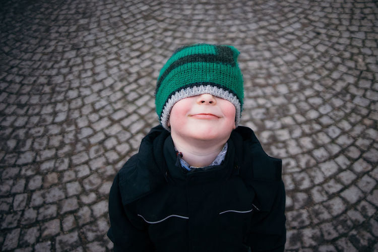 Boy with eyes covered by knit hat on cobblestone street