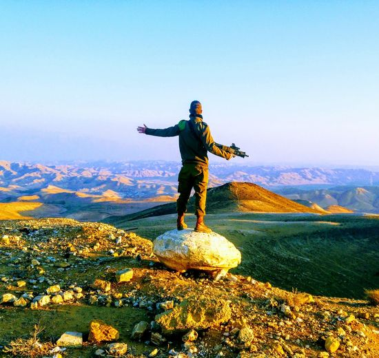 Rear view of young man with arms outstretched standing on mountain against sky during sunset