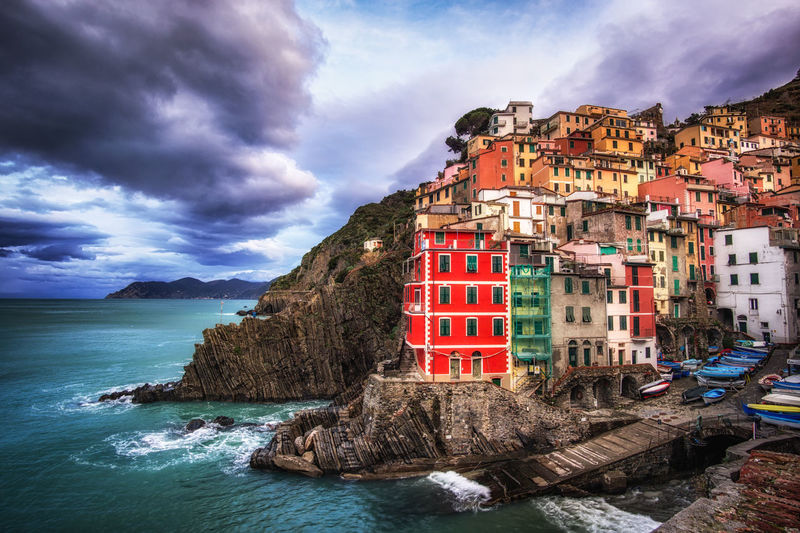 Colorful town of riomaggiore in cinque terre, Italy. The photo is taken during winter right after the sunrise. I captured the storm clouds approaching coastline. Architecture Astrology Sign Beauty In Nature Cinque Terre Cloud - Sky Day Italian Italy Landscape Nature No People Outdoors Postcard Riomaggiore Scenics Sea Sky Sunset Tourism Town Travel Travel Destinations Vacations Villa Village