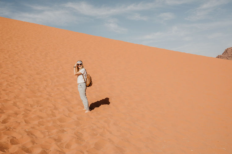 Young woman standing on sand dune in desert against sky