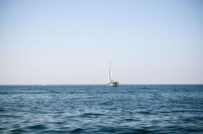 Sailboat Sailing On Sea Against Clear Sky