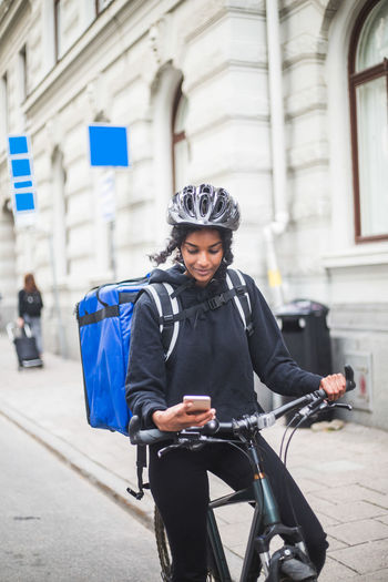 Young woman riding bicycle on street in city