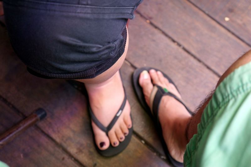 Low Section Of People Wearing Slippers On Boardwalk