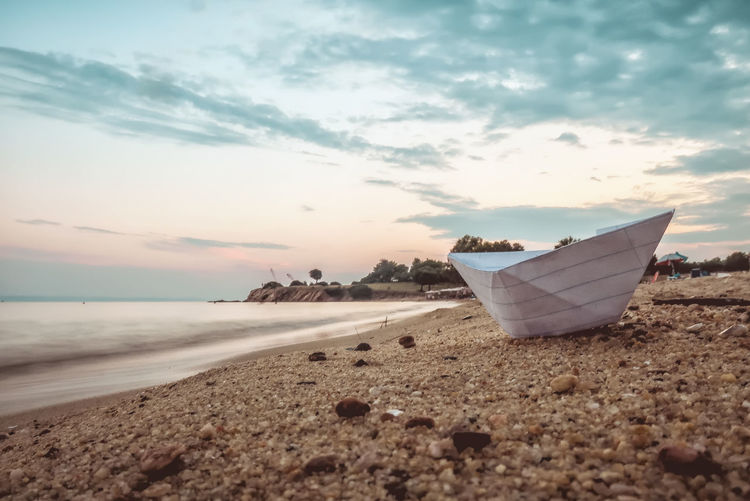 Paper boat on a beach Traveling Summer Sea Beach Water Sunset Nature Sky Summertime Travel Tourism Vacation Outdoors Boat Tranquility Paper Sand Transportation Paper Boat No People Boats⛵️ Tranquil Scene Nautical Vessel Cloud - Sky Scenics - Nature Close-up Floating On Water