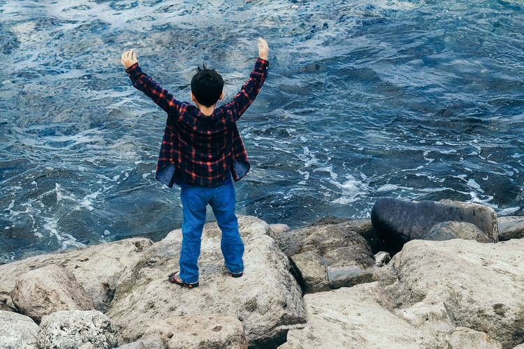 Rear view of boy standing on rock against sea