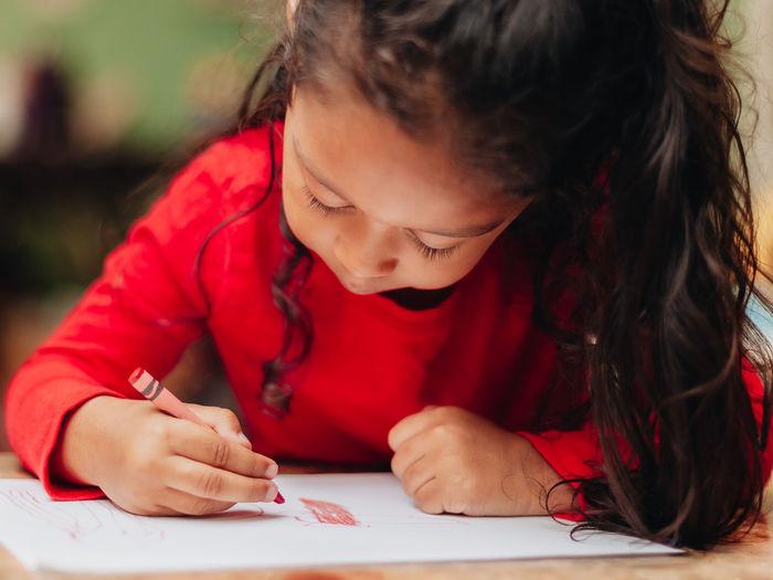 Cute girl drawing at home