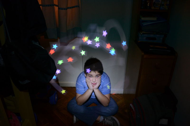 Portrait Of Sad Boy Against Star Shape Light Paintings At Home