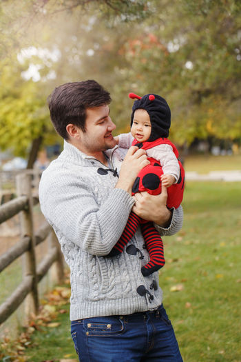 Father carrying baby daughter while standing in park