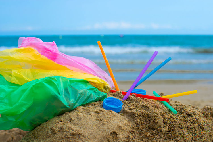 Close-up of multi colored umbrella on beach