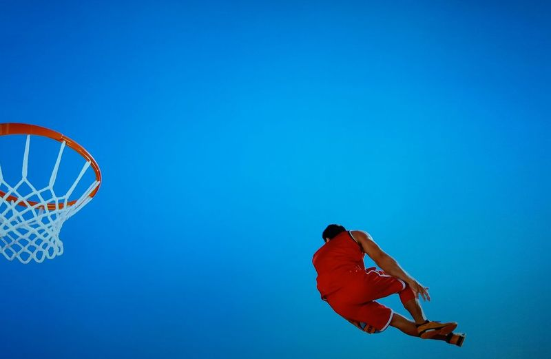 Low Angle View Of Male Basketball Player Jumping Against Clear Blue Sky