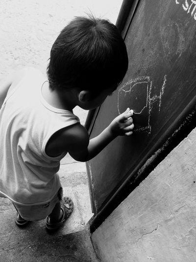 Side view of boy drawing on blackboard
