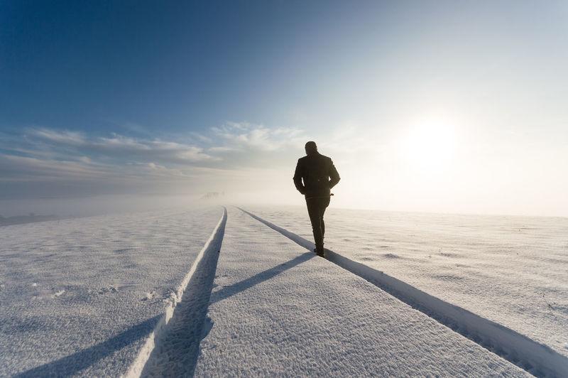 Teenager walking on snow against sky