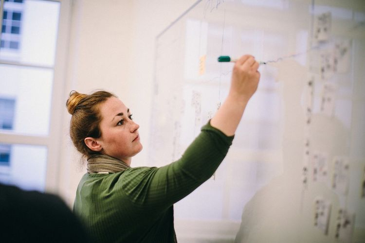 Teacher Writing On Whiteboard In Classroom