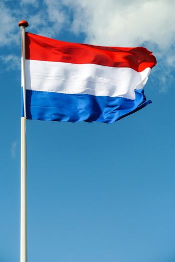 Low angle view of dutch flag waving against blue sky