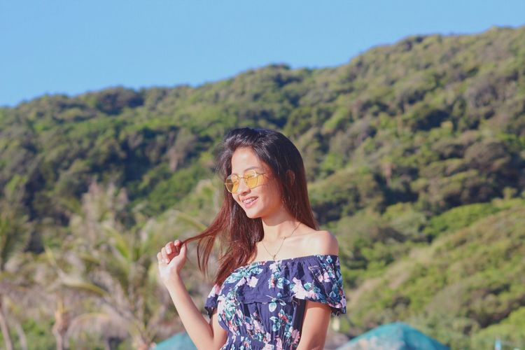 Smiling young woman wearing sunglasses while standing against mountain during sunny day