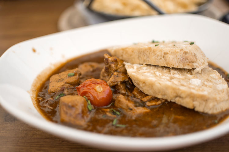 Traditional Goulash with knedle in a white bowl of beef stew on the wooden table, Germany menu Food Ready-to-eat Freshness Table No People Bowl Vegetable Bread Plate Meat Healthy Eating Wellbeing Traditional Knedle Goulash Beef Stew Germany Menu Dish Delicious