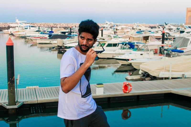 Portrait of young man standing in boat yard