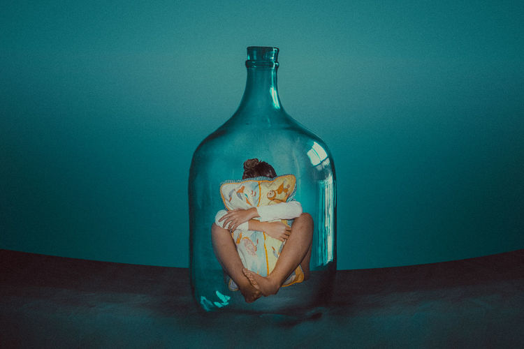 Digital composite image of young woman embracing pillow while sitting in bottle against wall
