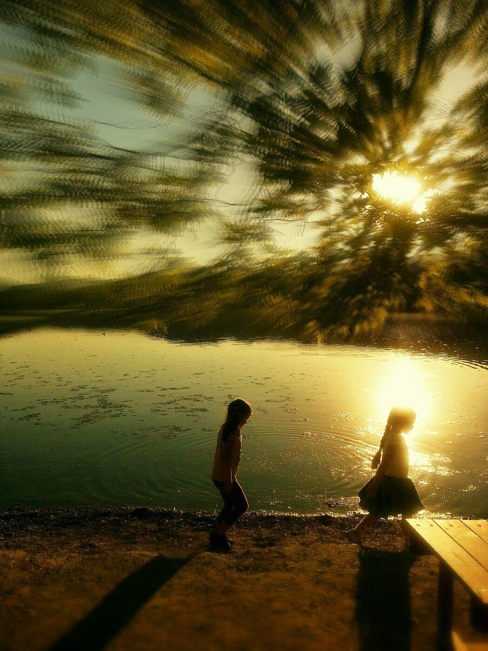 water, full length, sunset, silhouette, lifestyles, leisure activity, sunlight, reflection, beach, sea, sun, sky, walking, pier, standing, men, nature, shore