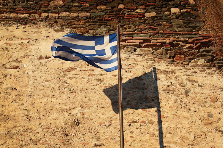 Low angle view of greek flag with shadow against sky