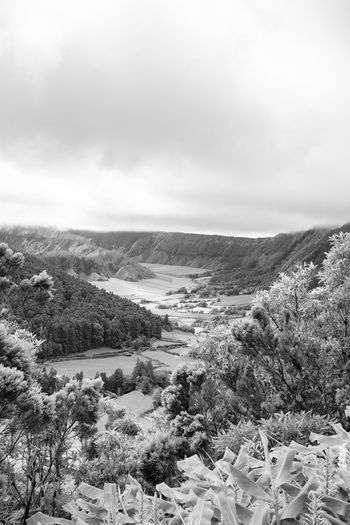 Black and white view of two smaller calderas inside of a larger one on the island of Sao Miguel in the Azores. Sete Cidades Azores Azorean Açores Sao Miguel Crater Caldera Caldeira Alferes Village Lagoa Azul Verde Clouds Farm Pasture Hike View Landscape Tourism Trek Volcano Black And White