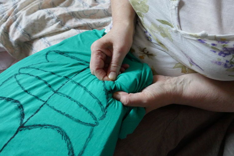 Midsection of woman sewing fabric at home