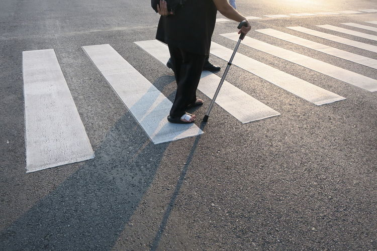 Low Section Of Men Walking On Zebra Crossing During Sunny Day