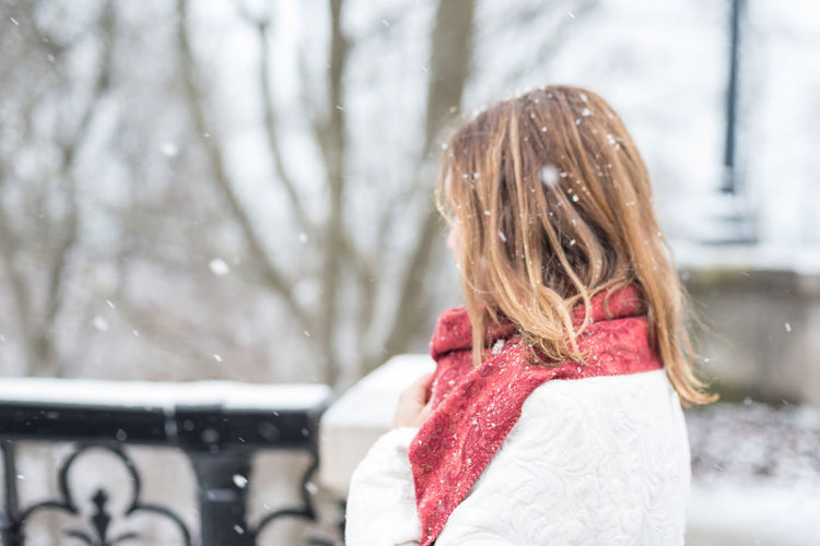 Close-up of girl with snow on tree