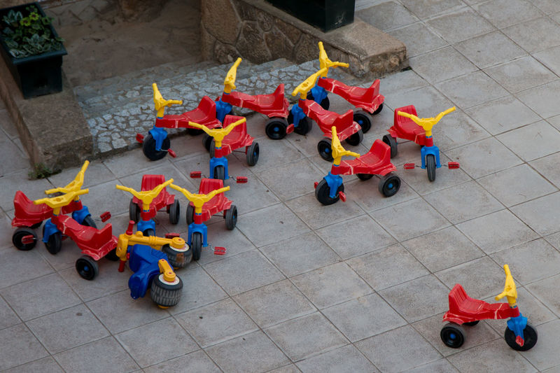 High Angle View Of Red And Yellow Tricycles At Playground