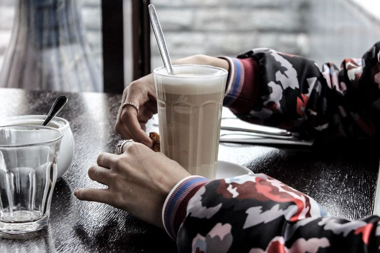 Cropped hands of person with hot chocolate on table in restaurant