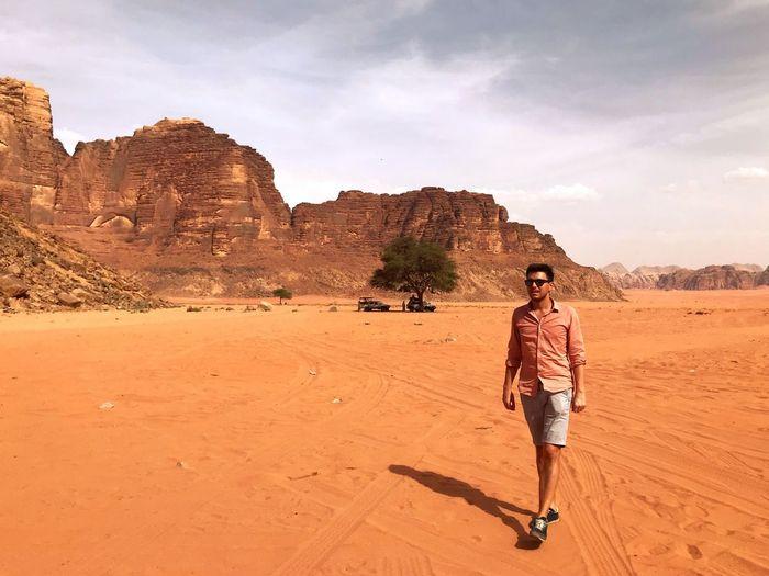 Young adult in casual clothing, walking around wadi rum desert in jordan