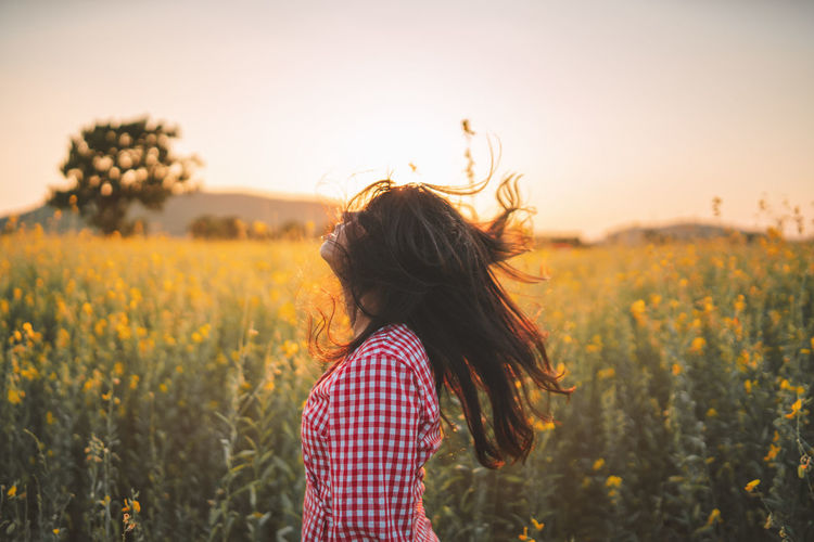 Woman tossing hair while standing amidst plants during sunset