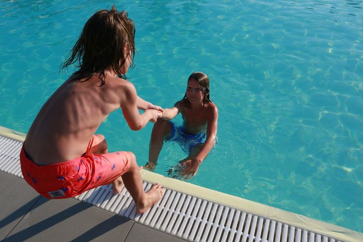 Rear view of shirtless boy pulling friend from swimming pool